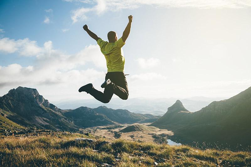 O homem pulando em triunfo em cima de uma colina