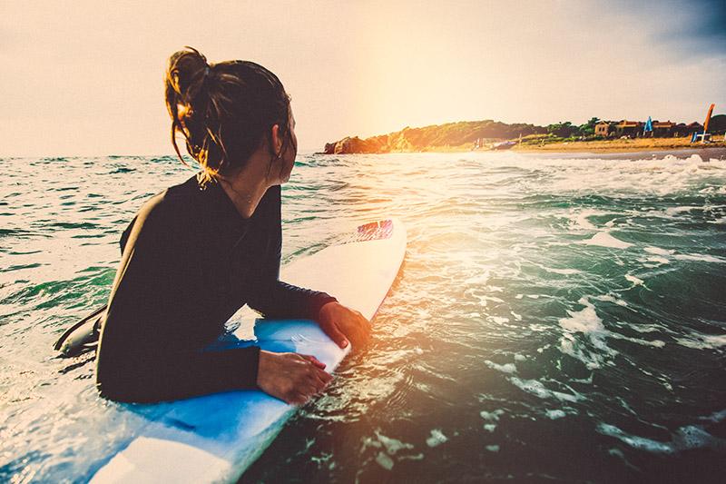 Mulher em uma placa de surf no mar